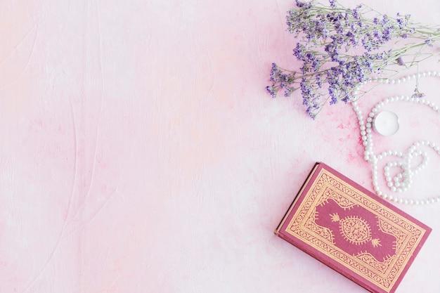 Libro del corán con pequeñas flores de color púrpura