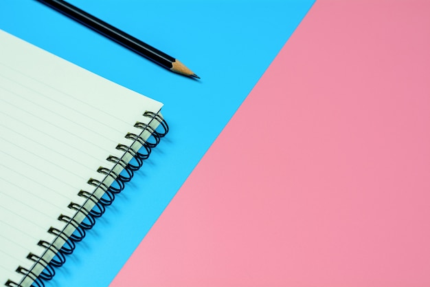 Libro diario y un lápiz sobre fondo azul y rosa con espacio de copia. - vista superior.