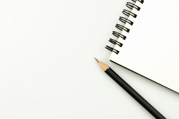 Libro diario y un lápiz sobre fondo de escritorio blanco con espacio de copia