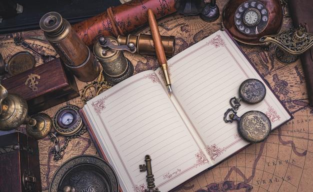 Libro diario y pluma en el mapa antiguo