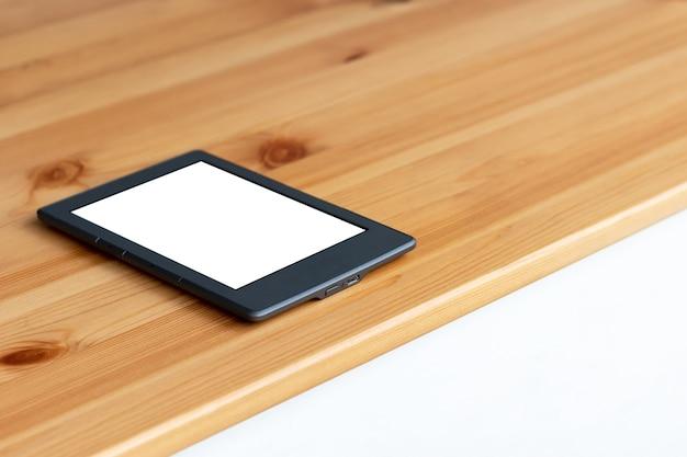 Libro electrónico gris o tableta con pantalla de maqueta en blanco en blanco sobre una mesa de madera.