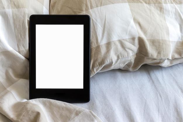 Un libro electrónico negro moderno con una pantalla vacía en blanco sobre una cama blanca y beige. tableta de maqueta en ropa de cama