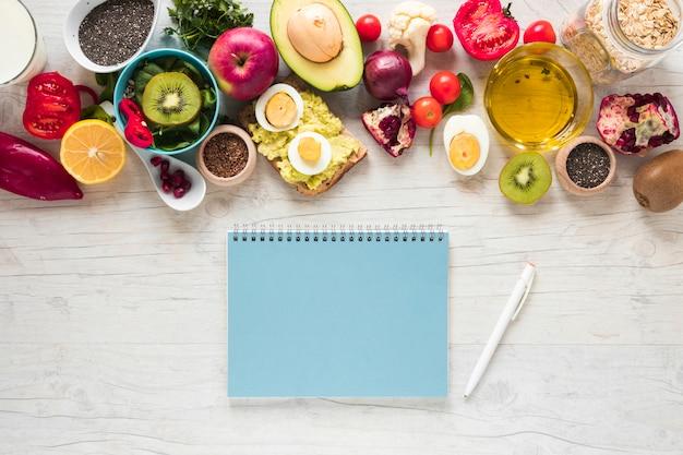 Libro de espiral bolígrafo; frutas frescas; pan tostado; verduras e ingredientes sobre fondo blanco con textura