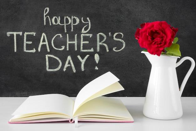 Libro y flores feliz día del maestro concepto