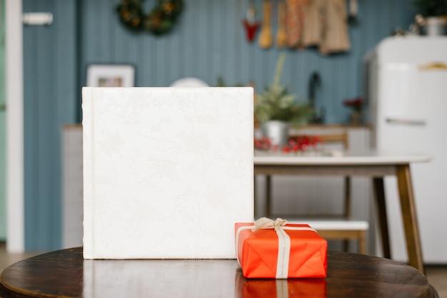 Libro fotográfico de boda blanco con una cubierta de cuero con encaje y una caja roja de regalo de navidad sobre la mesa