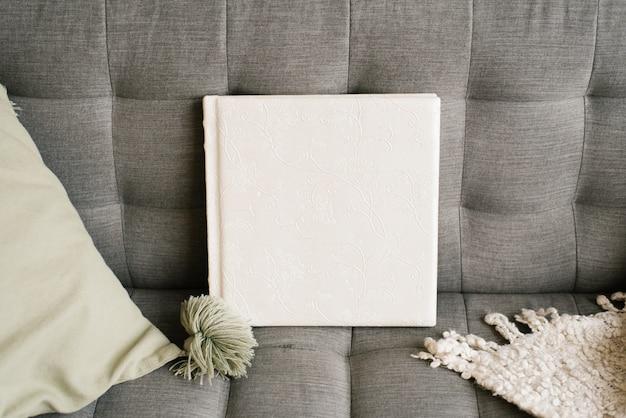 Libro fotográfico de boda blanco en una funda de cuero en el sofá