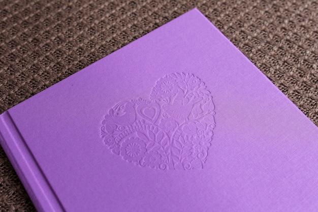 Libro de fotos con funda textil. color violeta con estampado decorativo.