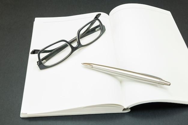 Libro con gafas y una pluma