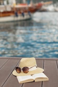 Libro gafas de sol y un sombrero de pie en la orilla de un puerto