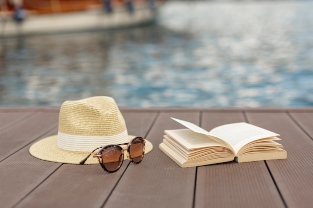 Libro de gafas de sol y un sombrero de pie en la orilla de un puerto