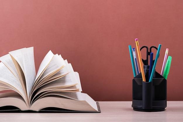Un libro grande y grueso con las páginas extendidas como un abanico y un soporte con bolígrafos.
