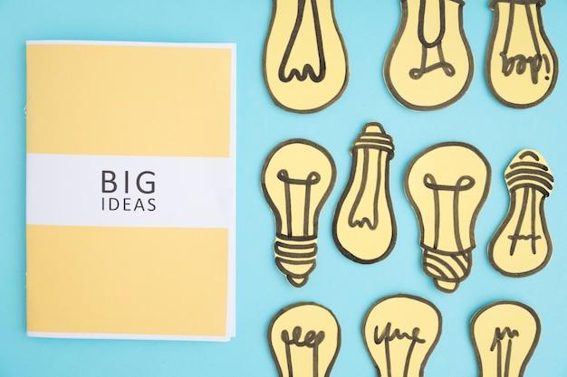 Libro de grandes ideas con muchos focos de luz amarilla sobre fondo azul