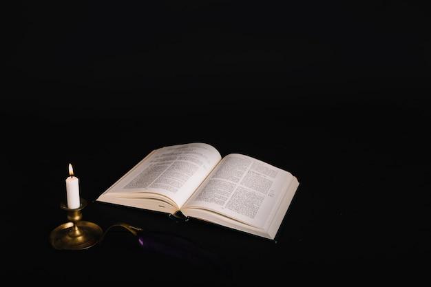Libro con hechizos y vela encendida cerca