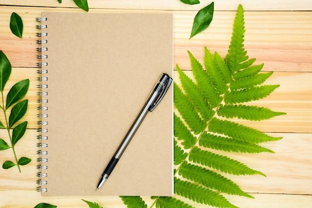 Un libro con hojas verdes en mesa de madera.