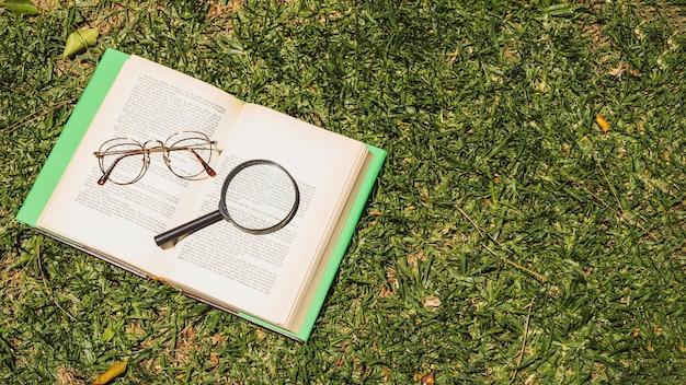 Libro con implementos ópticos sobre hierba verde.