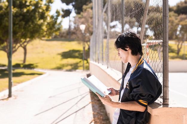 Libro de lectura del alumno étnico en el callejón en el parque