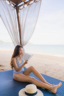 El libro de lectura asiático joven hermoso de la mujer del retrato con sonrisa feliz se relaja en silla de la cama del salón en el océano del mar de la playa para el ocio