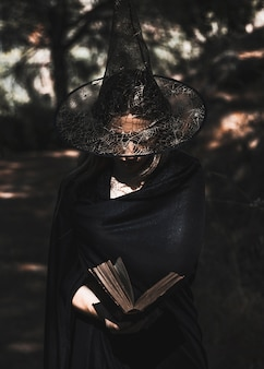 Libro de lectura de la bruja en el matorral durante el día