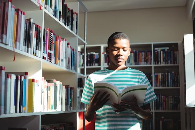Libro de lectura de colegial atento en biblioteca
