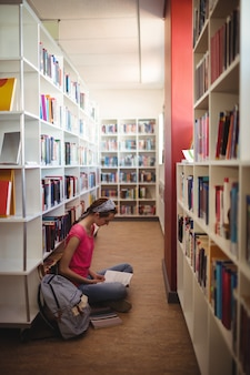 Libro de lectura de colegiala atento en biblioteca