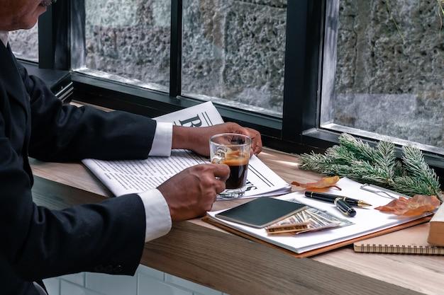 Libro de lectura del director empresarial y café de consumición.