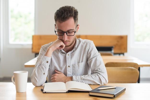 Libro de lectura enfocado del estudiante masculino en el escritorio en sala de clase