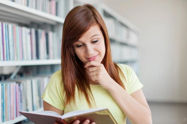 Libro de lectura de estudiante universitario en biblioteca