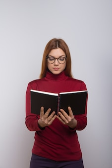 Libro de lectura de estudiante universitario femenino enfocado