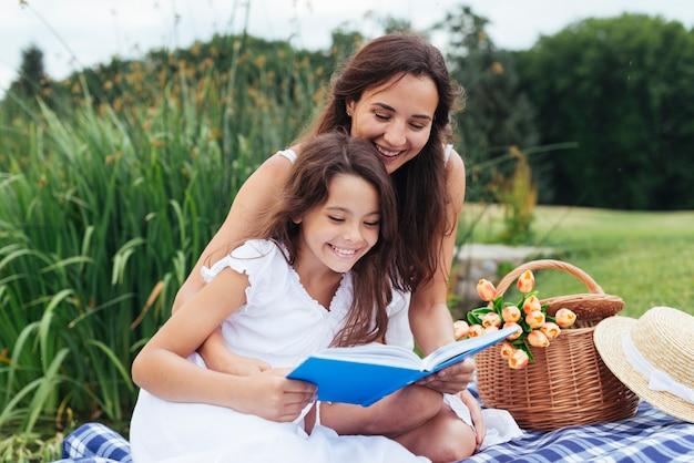 Libro de lectura feliz de la madre y de la hija en la comida campestre