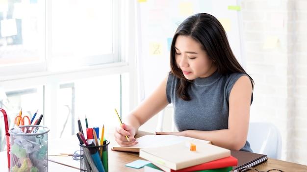 Libro de lectura femenino asiático del estudiante universitario en la tabla
