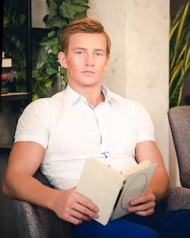 Libro de lectura guapo está sentado en el sofá.