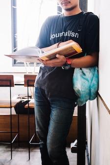 Libro de lectura del hombre de la cosecha cerca de la pared