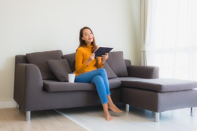 Libro de lectura de joven asiática en sofá