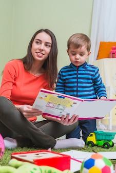 Libro de lectura de la madre con hijo en la habitación de los niños