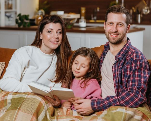 Libro de lectura de madre y padre en casa con hija