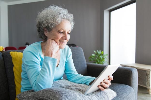 Libro de lectura maduro contento de la mujer en la tableta
