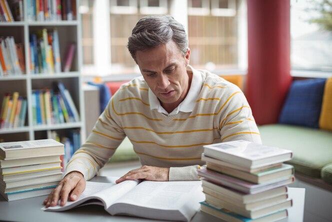 Libro de lectura del maestro de escuela atento en la biblioteca