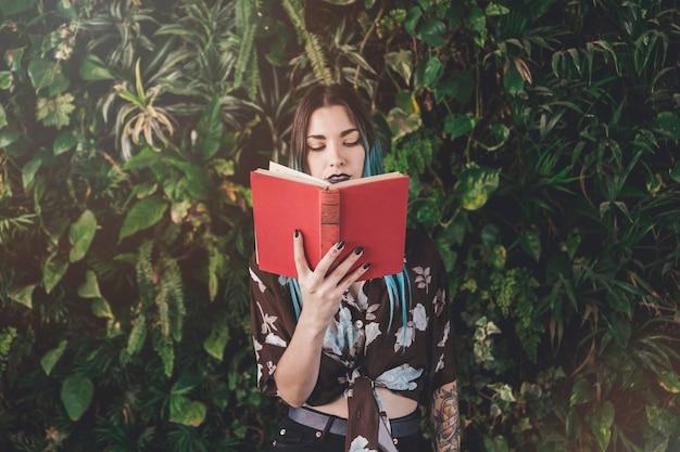Libro de lectura moderno de la mujer joven que se coloca delante de las plantas crecientes