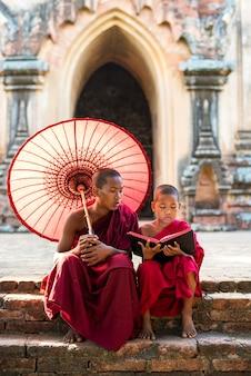Libro de lectura de monje novicio de myanmar fuera del templo de myanmar