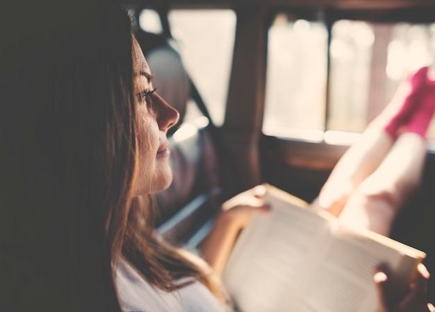 Libro de lectura de la muchacha dentro del concepto de coche