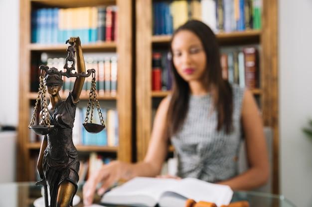 Libro de lectura de la mujer afroamericana en la mesa con la estatua en la oficina