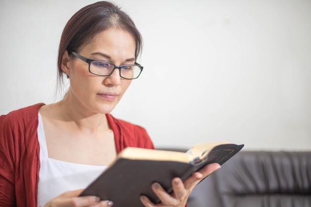 Libro de lectura de mujer asiática en casa. espiritualidad y religión, conceptos religiosos