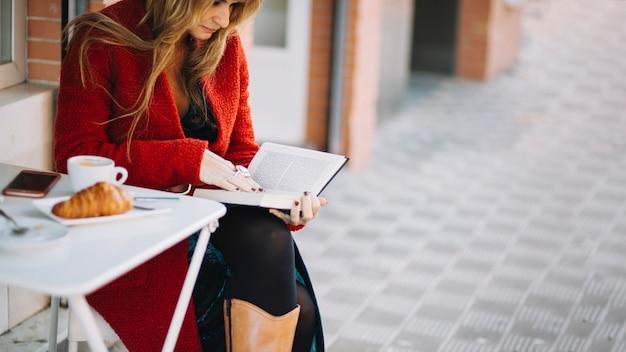 Libro de lectura de la mujer en el café al aire libre