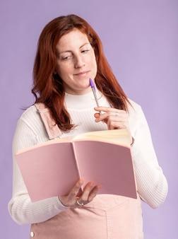 Libro de lectura de mujer embarazada de ángulo bajo