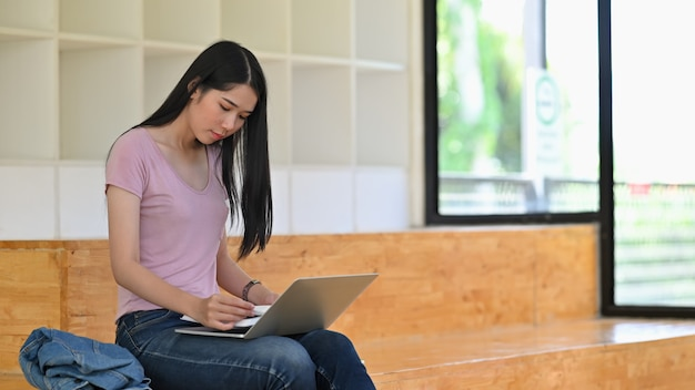 Libro de lectura de la mujer joven con la computadora portátil en sitio de biblioteca.