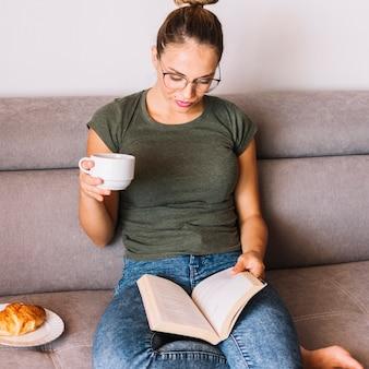 Libro de lectura de la mujer joven mientras que desayunando