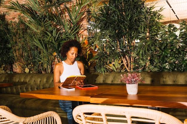 Libro de lectura de la mujer joven que se sienta cerca de la tabla en el restaurante
