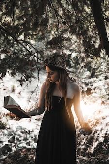 Libro de lectura de mujer joven con vela en mano en el bosque
