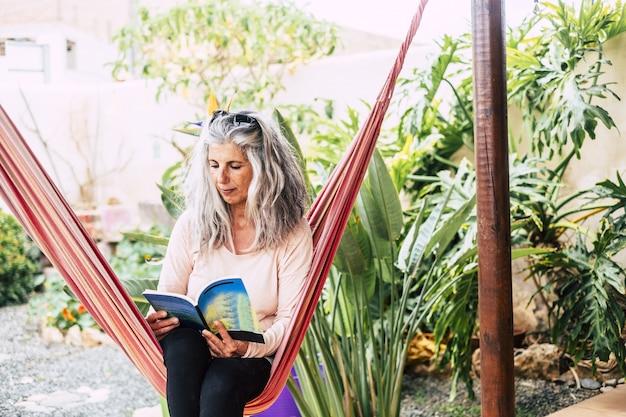 Libro de lectura de la mujer mayor que se sienta en la hamaca en el patio delantero o trasero. anciana relajante en el jardín. anciana sentada en una hamaca de columpio en el jardín de su casa y leyendo un libro