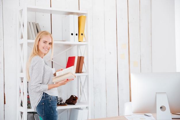 Libro de lectura de mujer de negocios rubia sonriente mientras está de pie en la oficina